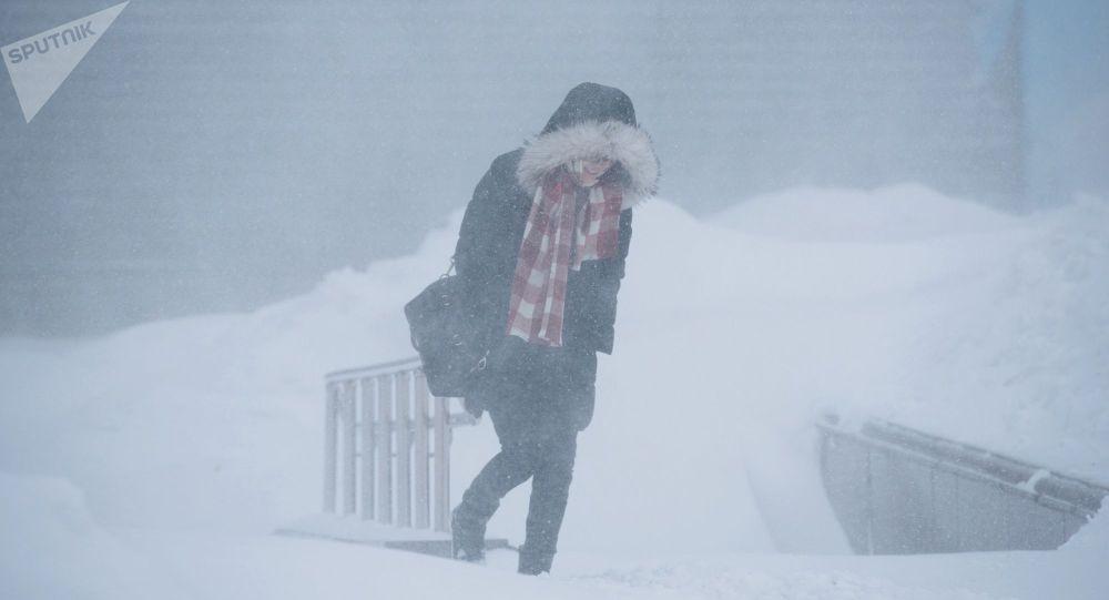 Девушка идет по улице во время снежной метели. Архивное фото