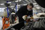 Сотрудник центра по обслуживанию автомобилей проводит замену масла в автомобиле. Архивное фото