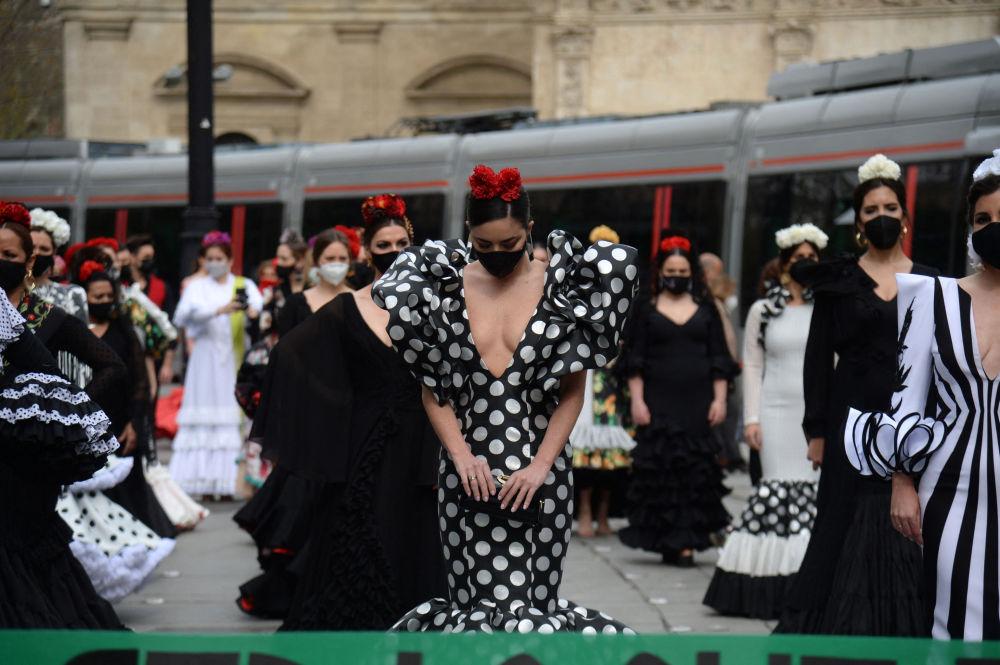 Женщины, одетые в платья фламенко, принимают участие в акции протеста, чтобы обозначить трудности, с которыми сектор моды фламенко сталкивается из-за ограничений, связанных с коронавирусом, в Севилье