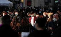 Люди в защитных масках идут по главной торговой улице Виа-дель-Корсо в Риме, Италия