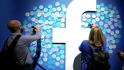 Кишилер Facebook логотибине заметкаларды жазып жатышат. Архив