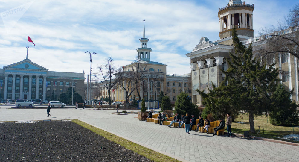 Люди сидят на скамейках у здания Международного университета Кыргызстана в Бишкеке. Архивное фото