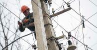 Сотрудник Северэлектро проводит ремонтные работы на линии электропередач. Архивное фото