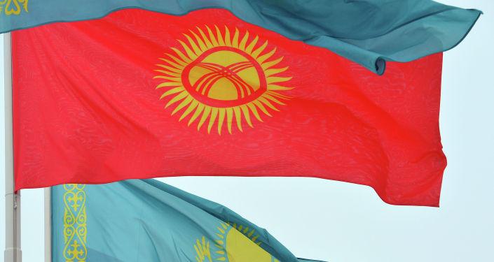 Флагштокто Кыргызстан менен Казакстандын туулары илинген, килем төшөлүп, ардак кароол тизилип турат