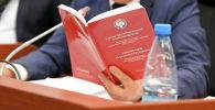 Депутат ЖК изучает Конституцию Кыргызской Республики во время заседания