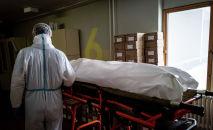 Медициналык кызматкер COVID-19дан көз жумган адамдын жанында. Архив