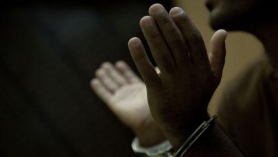 Обвиняемый в наручниках во время допроса. Архивное фото