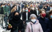 Люди в защитных масках идут улице в Риме, Италия