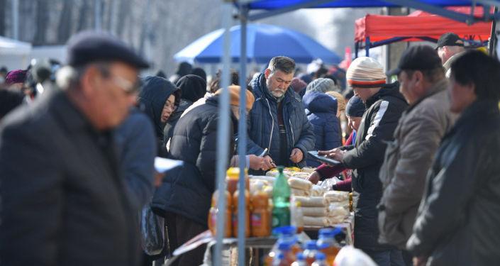 Люди покупают товары в сельскохозяйственной ярмарке в Бишкеке