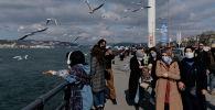 Люди в защитных масках гуляют по Босфору во время вспышки коронавирусной болезни (COVID-19) в Стамбуле. Архивное фото