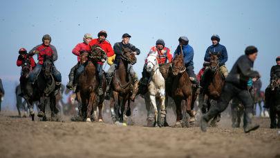 Участники состязания игры аламан улак борются за тушу теленка на территории поселка Дача СУ. 6 марта 2021 года