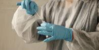 Медицинский работник держит пробирку с мазком из носа в центре тестирования COVID-19. Архивное фото