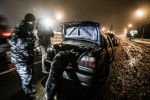 Сотрудник правоохранительных оргавно досматривает багажник автомобиля. Архивное фото