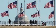 Вашингтондогу Америка желектеринин фонунда Капитолий имаратынын сыртындагы адамдар. Архив