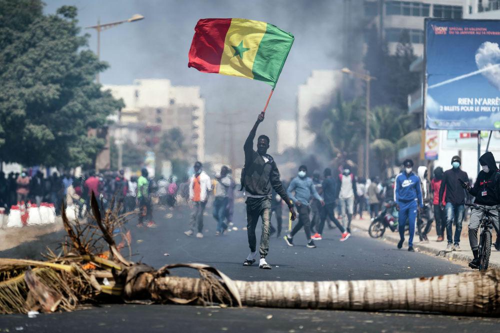 Демонстрант машет сенегальским национальным флагом во время протестов в поддержку главного лидера оппозиции и бывшего кандидата в президенты Усмана Сонко в Дакаре, Сенегал. 3 марта 2021 года