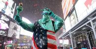 Мужчина в костюме Статуи Свободы и покрытый флагом США на Таймс-сквер в Нью-Йорке. Архивное фото