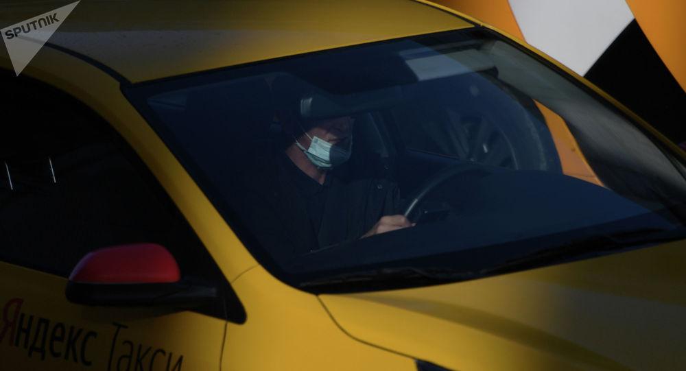 Водитель в защитной маске за рулем такси. Архивное фото