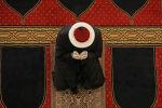 Священнослужитель в перчатках молится в мечети. Архивное фото