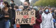 Девушка с плакатом перед Бранденбургскими воротами во время демонстрации климатических активистов в Берлине (Германия)