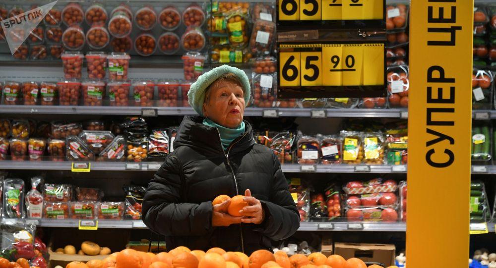Москванын супермаркетинде апельсин сатып алып аткан аял. Архивдик сурөт
