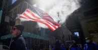 Сторонник бывшего президента США Дональда Трампа держит флаг, когда он присутствует на митинге на 5-й авеню перед башней Трампа