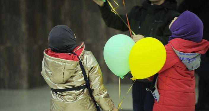 Дети с шариками в руках в Бишкекском аэропорту Манас после возвращения на родину из Ирака. 16 марта 2021 года