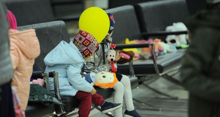 Дети с шариком и игрушками в Бишкекском аэропорту Манас после возвращения на родину из Ирака. 16 марта 2021 года