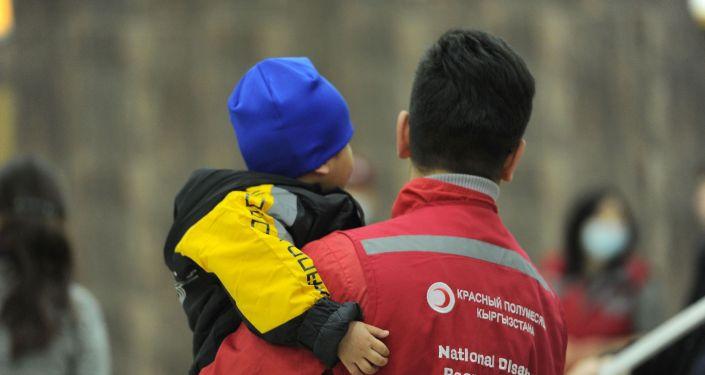 Сотрудник Красного полумесяца держит в руках ребенка, возвращенного на родину из Ирака, аэропорт Манас, Бишкек. 16 марта 2021 года