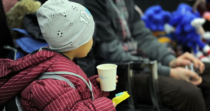 Ребенок со стаканом воды в Бишкекском аэропорту Манас после возвращения на родину из Ирака. 16 марта 2021 года