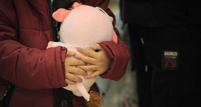 Ребенок с игрушкой в Бишкекском аэропорту Манас после возвращения на родину из Ирака. 16 марта 2021 года