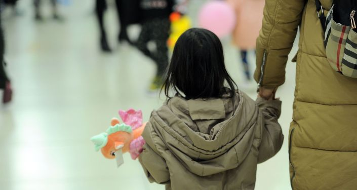 Ребенок с игрушкой держит за руку родителя после возвращения на родину из Ирака в Бишкекском аэропорту Манас. 16 марта 2021 года