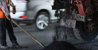 Работник дорожного хозяйства укладывает асфальт в поврежденном участке дороги. Архивное фото