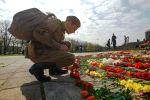 Мужчина возлагает цветы на мемориальном комплексе советских воинов-освободителей в парке Победы в Риге. Архивное фото