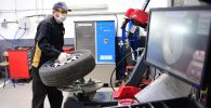 Сотрудник автоцентра производит шиномонтаж колеса. Архивное фото