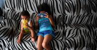 Брат с сестрой сидят на диване дома. Архивное фото