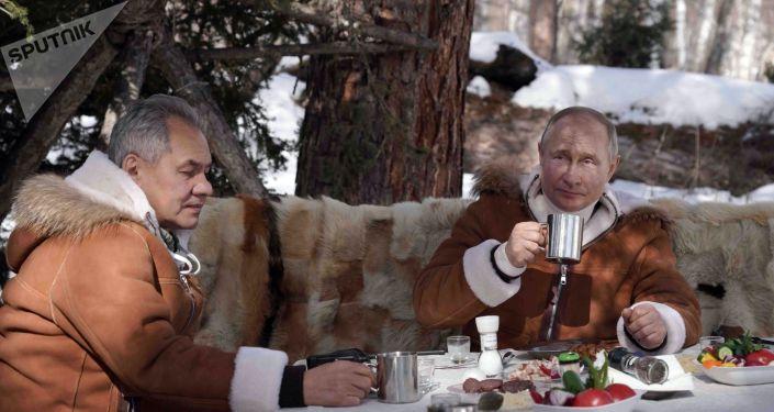 Президент РФ Владимир Путин и министр обороны РФ Сергей Шойгу (слева) во время отдыха в тайге.
