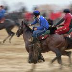 Игрок Достука (в красном) преследует кокбориста таласской команды. Его задача — помешать сопернику бросить улак.