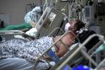 Медицинский работник оказывает помощь пациенту с COVID-19 в больнице