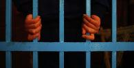 Заключенный держится за решетку. Архивное фото