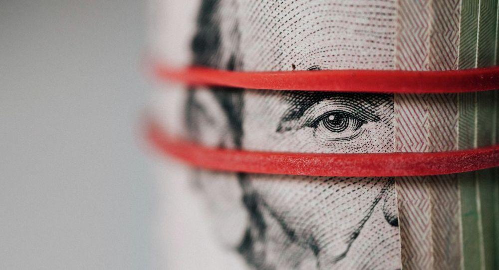 Доллары США перетянуты резинкой. Иллюстративное фото