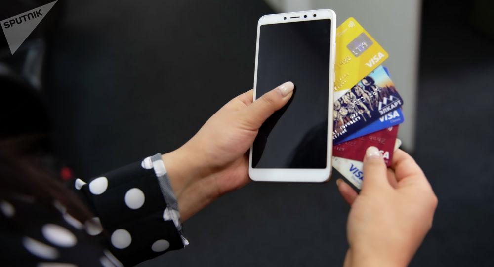 Смартфон и банковские карточки в руках у девушки. Иллюстративное фото