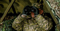 Военнослужащий смотрит в бинокль. Архивное фото