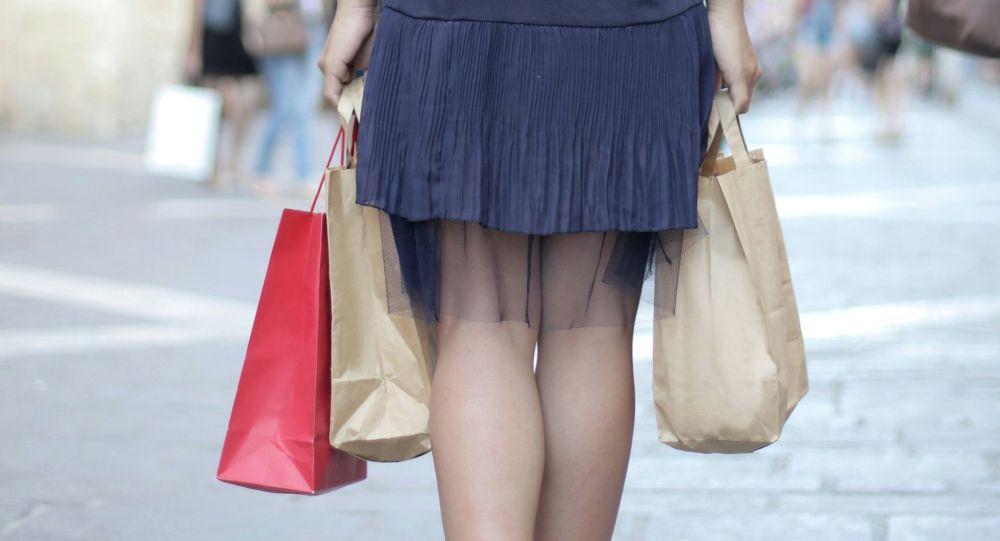 Девушка идет по улице с сумками. Иллюстративное фото