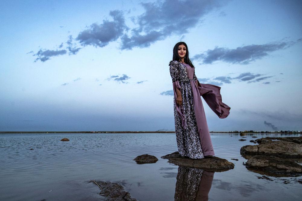 Девушка в сирийской национальной одежде фотографируется на берегу реки в провинции Хасака. 21 марта 2021 года