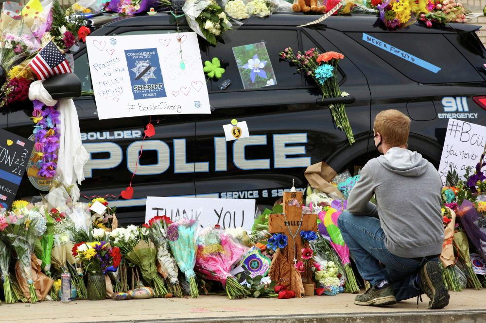 Мужчина возлагает цветы к полицейской машине офицера, который скончался во время стрельбы в продуктовом магазине King Soopers в Боулдере, Колорадо, США. 24 марта 2021 года.