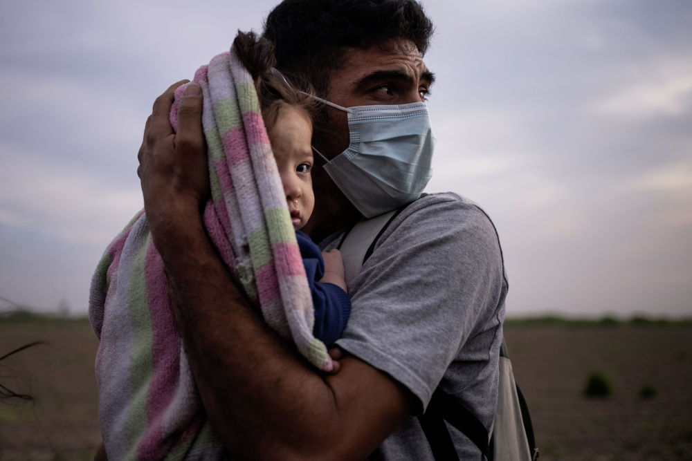 Мужчина из Гондураса со своей дочерью на берегу реки Рио-Гранде в США. 25 марта 2021 г