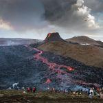 Туристы смотрят на лаву, стекающую из жерла вулкана Фаградальсфьяль в Исландии. 23 марта 2021 года