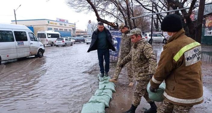 Сотрудники МЧС на пересечении проспекта Дэн Сяопина и улицы Алыкулова в Бишкеке во время затопления. 29 марта 2021 года