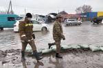 Сотрудники МЧС на пересечении улиц в Бишкеке во время затопления.