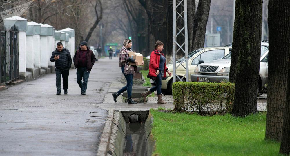 Люди идут в одном из улиц Бишкека во время дождливой погоды